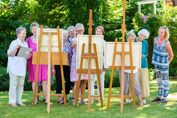 Senior women painting on canvas during sunny day.