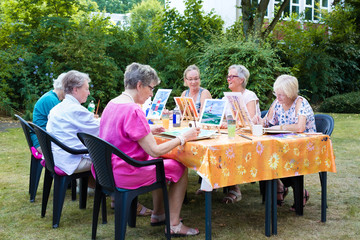Senior ladies attending art classes outdoors.