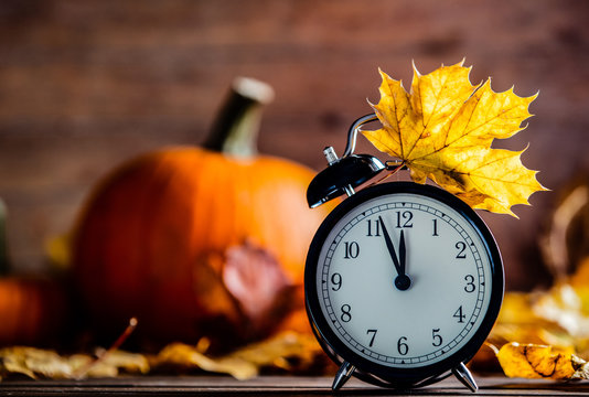 Vintage alarm clock and maple tree leaves with pumpkins on yellow wooden background with bokeh. Autumn season image style for Thaksgiving holiday