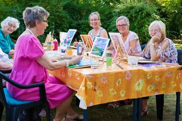 Happy group of senior ladies enjoying art class.