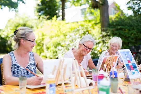Happy elderly women attending an outdoor art class.