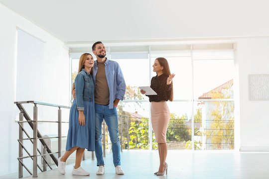 Female real estate agent showing new house to couple, indoors