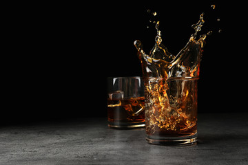Splashing golden whiskey in glass with ice cubes on table. Space for text