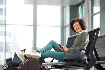 african american woman sitting on bench with luggage and mobile phone