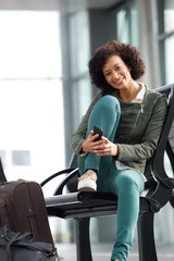 african american woman sitting at station with bags and mobile phone