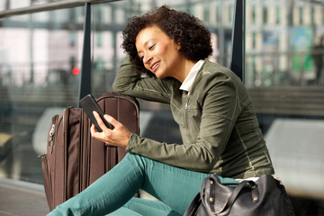 african american woman sitting at station with suitcase and mobile phone
