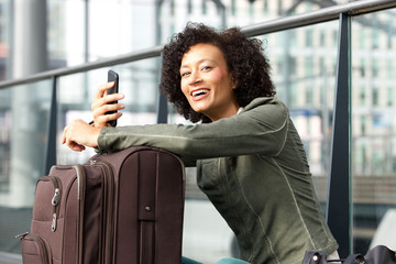 happy african american woman with suitcase and cellphone at station