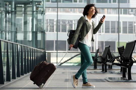 Full body side of travel woman walking at station with suitcase and  cellphone