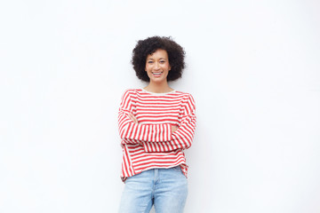 happy african american woman smiling with arms crossed against white wall