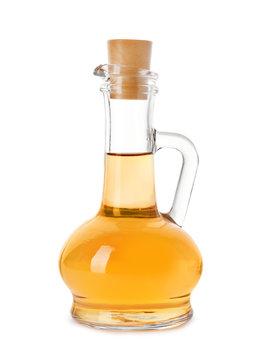 Glass jug of apple vinegar on white background