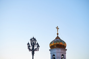A golden dome and a cross of a chirch with a street lamp with blue sky on the background