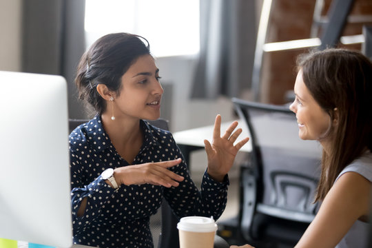 Friendly female colleagues having good relationships, pleasant conversation at workplace during coffee break, smiling young woman listen talkative coworker, discussing new project, talking in office