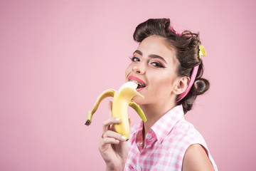pinup girl with fashion hair. pin up woman with trendy makeup. banana dieting. retro woman eating banana. pretty girl in vintage style, copy space. So tasty