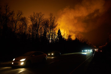 Forest fire with smoke and a road with cars at night, view from the distance