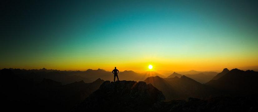 Man reaching summit enjoying freedom and looking towards mountains sunrise.