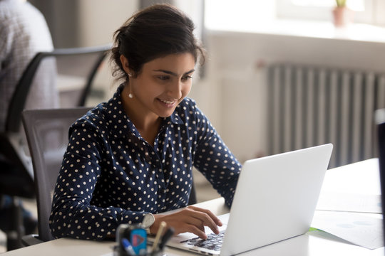 Smiling Indian female employee using laptop at workplace, looking at screen, focused businesswoman preparing economic report, working online project, cheerful intern doing computer work, typing