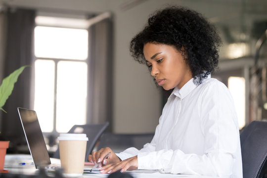 Serious African American woman working with documents at workplace, checking bills, financial reports, making notes with pen in hand, focused female student writing research work, preparing for exam