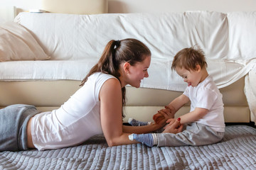 Cute small boy with Down syndrome playing with mother in home