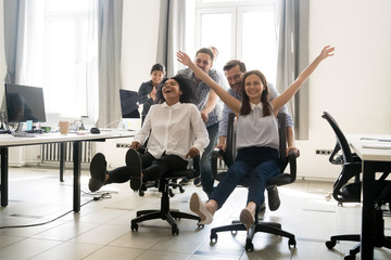 Happy multiracial colleagues group having fun together, riding on chairs in office, diverse excited office workers enjoying break, laughing, engaged funny activity, celebrating corporate success