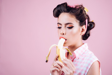 pin up woman with trendy makeup. retro woman eating banana. pinup girl with fashion hair. pretty girl in vintage style. banana dieting, copy space. i want you
