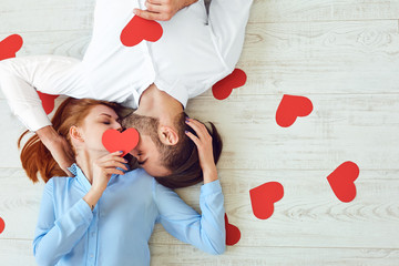 Couple kisses lying on a floor with a paper heart