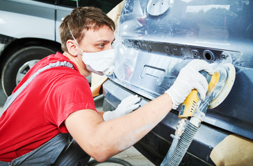 auto repairman grinding autobody