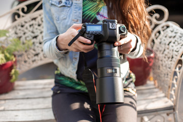 Close-up of female hands holding a professional camera. Female photographer with a professional camera.