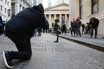 A man photographs the 'Fearless Girl' statue sits at its new location outside the NYSE near Wall St. in New York