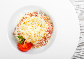 Fettuccine pasta with meat, ham, parmesan cheese, basil and tomato on plate on light wooden background, Italian cuisine. Ingredients on table