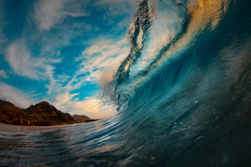 Giant surfing wave barreled at sunset ocean in Hawaii