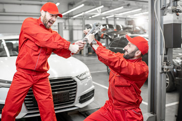 Funny portrait of two auto mechanics in red uniform fighting with wrenches in the car service