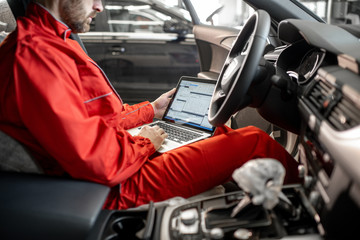 Auto mechanic in red uniform diagnosing car with computer sitting on the driver seat at the car service