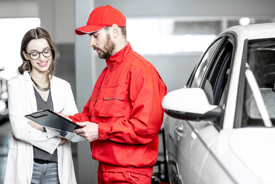 Young woman client with auto mechanic in red uniform standing with some documents at the car service