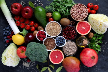 Healthy food concept. Vegetarian and vegan food: vegetables, fruits, seeds, legumes, leaf vegetables on dark background. Diet food. Top view.
