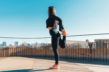 Fitness woman stretching and exercising outdoors in urban environment.