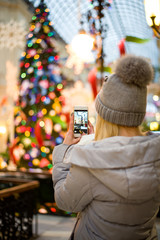 the girl in winter clothes make photo of the Christmas tree on the phone, a girl is taking pictures of Christmas tree on the phone (vertically, warm toned)