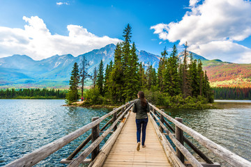 Young woman walking in a narrow wood bridge in front of an amazing scenario in Jasper National Park in Canada