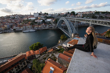 Woman with dreadlocks on the viewing platform opposite the Dom Luis I bridge, Douro river, Porto, Portugal.
