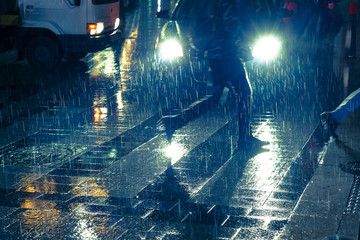 Backlit falling raindrops. Legs of people crossing the road against car headlight