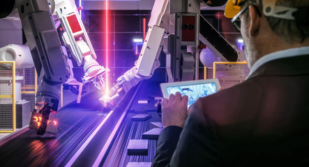 Smart automation industry robot in action welding metall while engineer uses his remote control table pc- industry 4.0 concept - 3D rendering