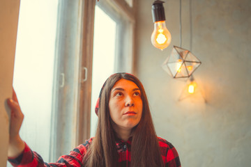Girl sitting on the window, hanging from the ceiling light bulb. Model posing at the window. Concept: idea and thought