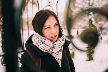 Portrait of a young woman. A smiling girl is walking around the winter city. The brunette  walks down the street.