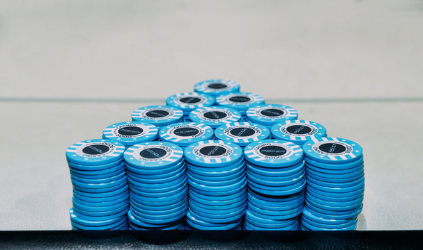 Pyramid consisting of piles of blue poker chips on table with copy space