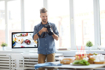 Portrait of successful photographer taking pictures of table with food while working in photo studio, copy space