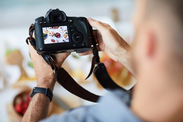 Above view closeup of unrecognizable photographer holding professional photo camera while taking pictures of food on table, copy space