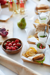 High angle background of rustic party table with various healthy food, fruits, sandwiches and lemonade drinks