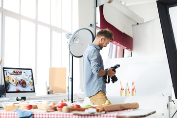 Portrait of smiling male photographer looking at pictures in camera while working in photo studio shooting food, copy space