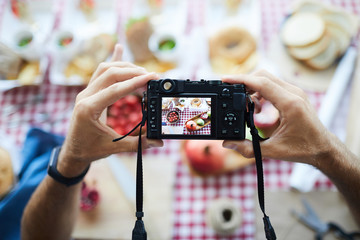 Top view closeup of photographer holding camera while taking pictures of food on picnic table, copy space