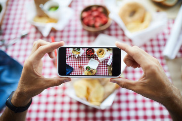 Top view closeup of unrecognizable man holding smartphone and taking pictures of food on picnic table, copy space