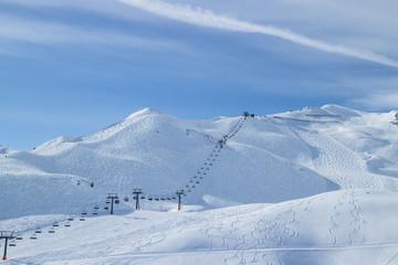 Sessellift mit Piste und Skispuren